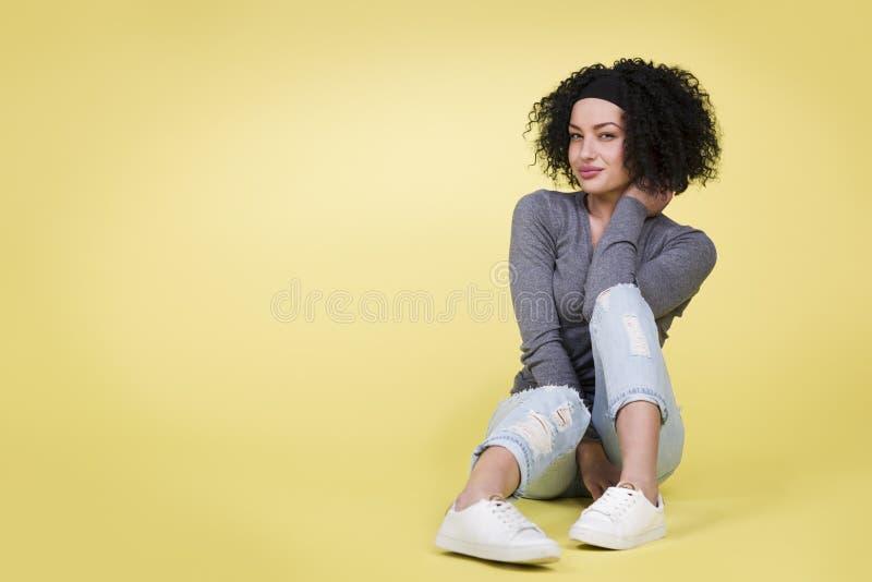 有性感的看起来的女孩坐被隔绝的黄色背景 免版税库存图片