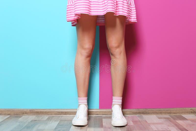 有性感的腿的妇女临近颜色墙壁 免版税库存图片