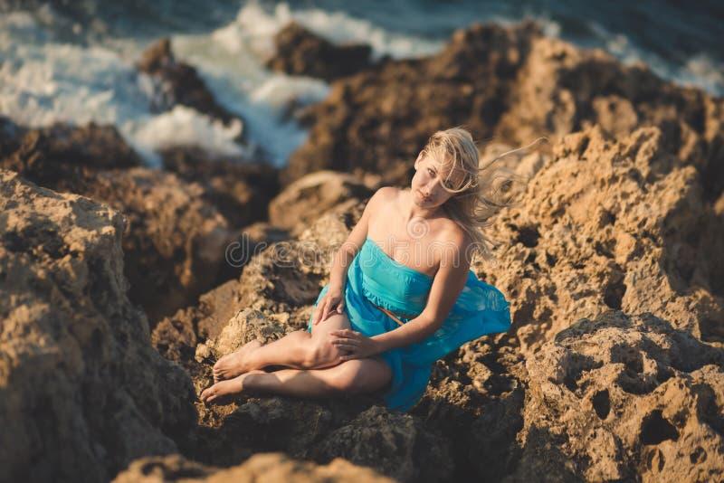 有性感赤裸腿肩膀和胳膊佩带的诱人的白肤金发的夫人妇女浅兰打开摆在的礼服享受假期  库存照片