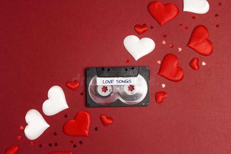 有恋爱歌曲和心脏的卡型盒式录音机磁带在红色背景 浪漫背景音乐概念 免版税库存图片