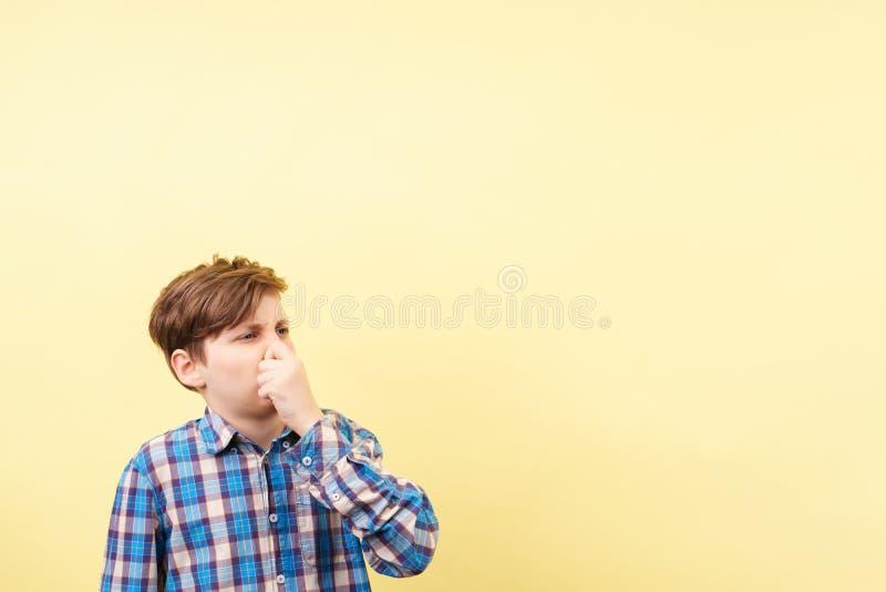 有恶心的面孔表示覆盖物鼻子的男孩 免版税图库摄影