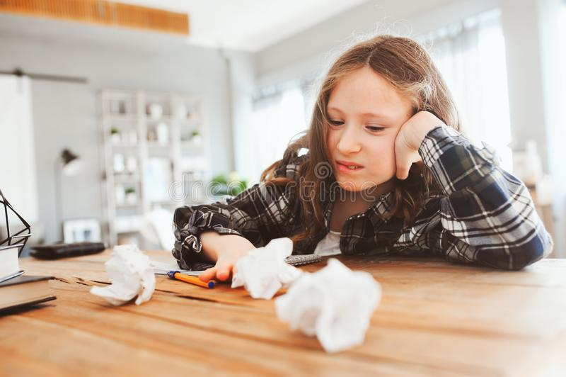 有恼怒和疲乏的儿童的女孩家庭工作的问题 免版税图库摄影