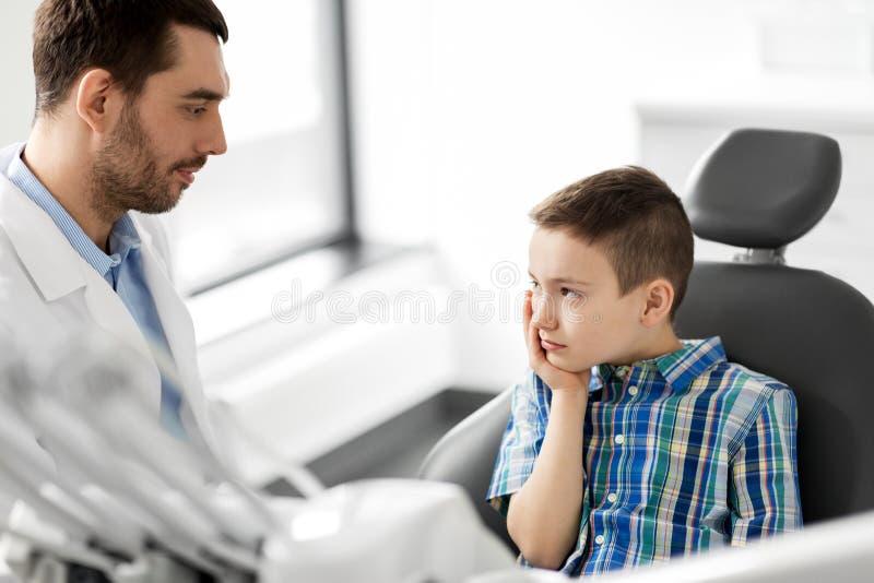 有患者的牙医有牙痛在诊所 免版税库存图片