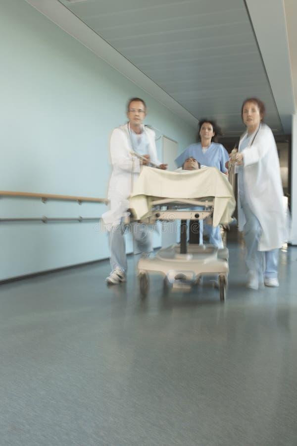 有患者的医师在医院走廊的盖尼式床的 库存照片