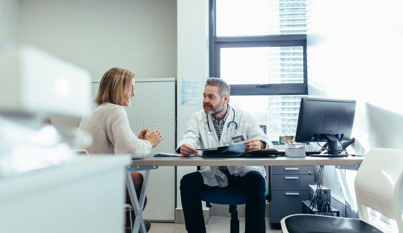 有患者的医生在咨询时在医疗办公室 免版税库存图片