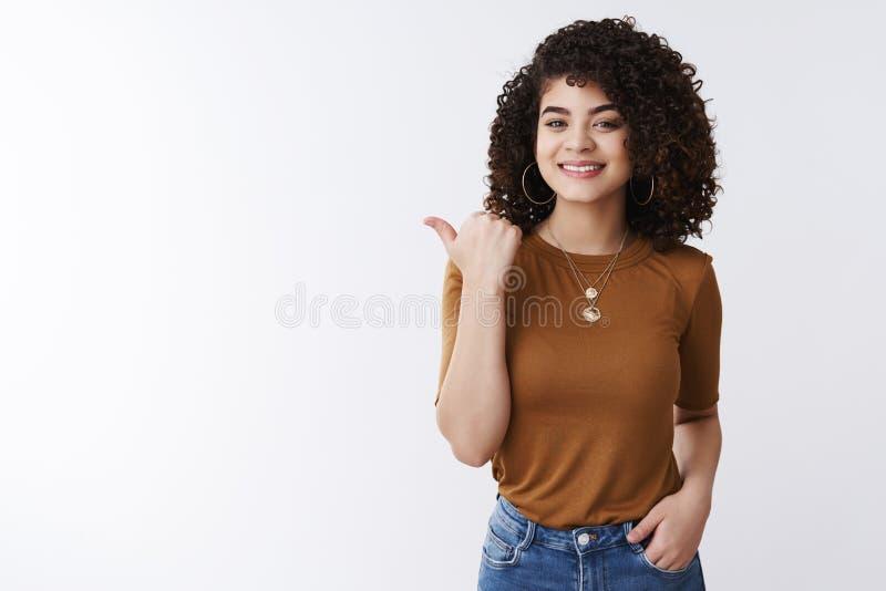 有您遇见我的朋友 指向拇指的高兴的悦目确信的时髦的女性卷曲黑发介绍产品 库存照片