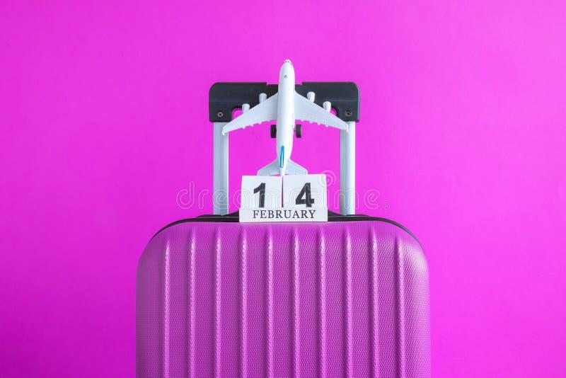 有情人节日期日历的在玫瑰色背景minimalistic假期概念的行李和飞机 免版税库存照片
