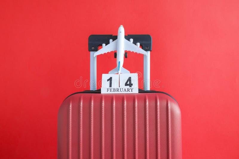 有情人节日期日历的在红色背景minimalistic假期概念的行李和飞机 库存照片