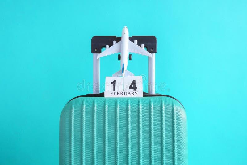 有情人节日期日历的在绿松石背景minimalistic假期概念的行李和飞机 库存图片