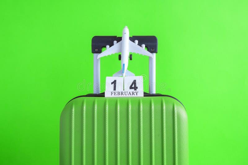 有情人节日期日历的在绿色背景minimalistic假期概念的行李和飞机 免版税库存图片