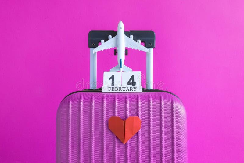 有情人节日期日历的有纸心脏的行李和飞机在玫瑰色背景minimalistic假期概念 图库摄影