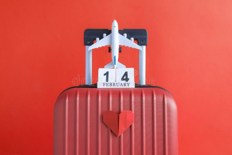 有情人节日期日历的有纸心脏的行李和飞机在红色背景minimalistic假期概念 库存照片