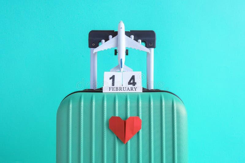 有情人节日期日历的有纸心脏的行李和飞机在绿松石背景minimalistic假期概念 图库摄影