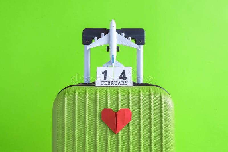 有情人节日期日历的有纸心脏的行李和飞机在绿色背景minimalistic假期概念 库存照片