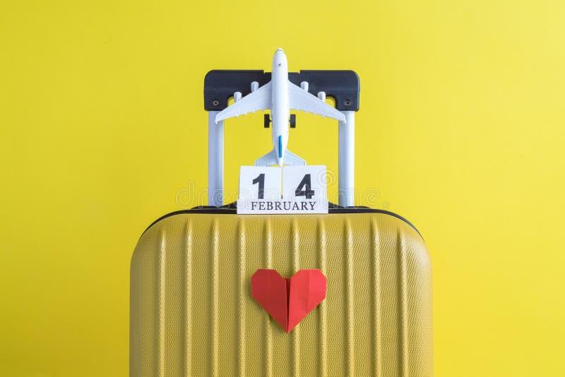 有情人节日期日历的有纸心脏的行李和飞机在黄色背景minimalistic假期概念 免版税库存图片