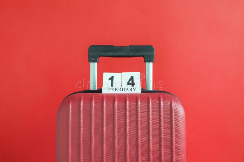 有情人节日期日历的行李在红色背景minimalistic假期概念 免版税库存图片