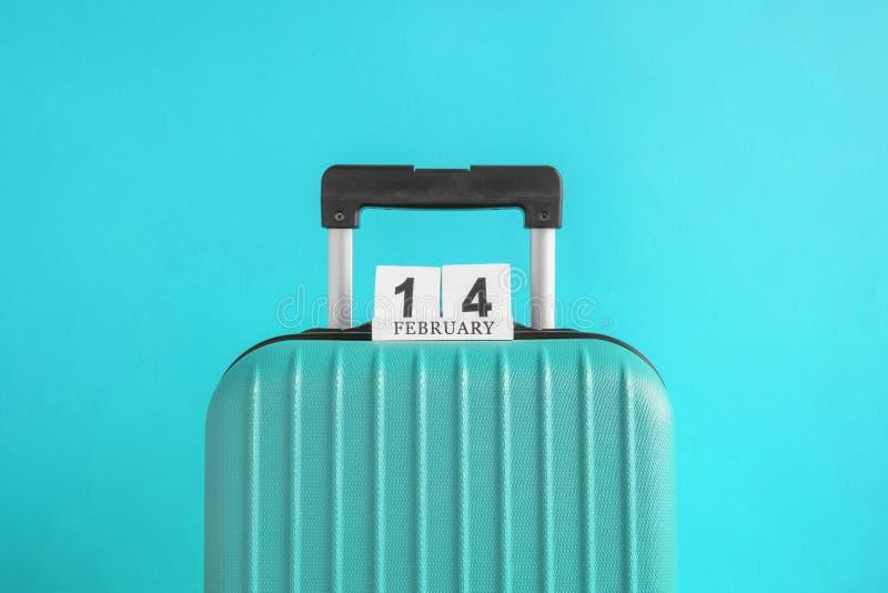 有情人节日期日历的行李在绿松石背景minimalistic假期概念 图库摄影