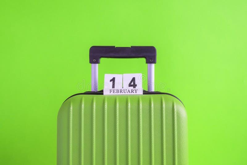 有情人节日期日历的行李在绿色背景minimalistic假期概念 库存照片