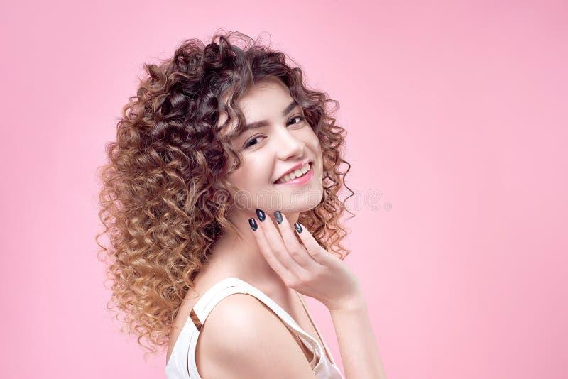 有惊人的发型卷曲亮光头发的愉快的微笑的少妇在白色衬衣 库存图片