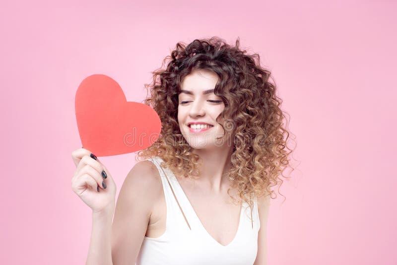 有惊人的发型卷曲亮光头发的愉快的微笑的少妇在白色衬衣 免版税库存图片