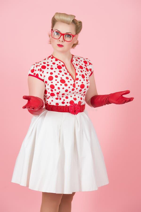 有惊奇的表示的可爱的困惑的白种人女性用手和glassed姿势反对粉红彩笔演播室背景 图库摄影