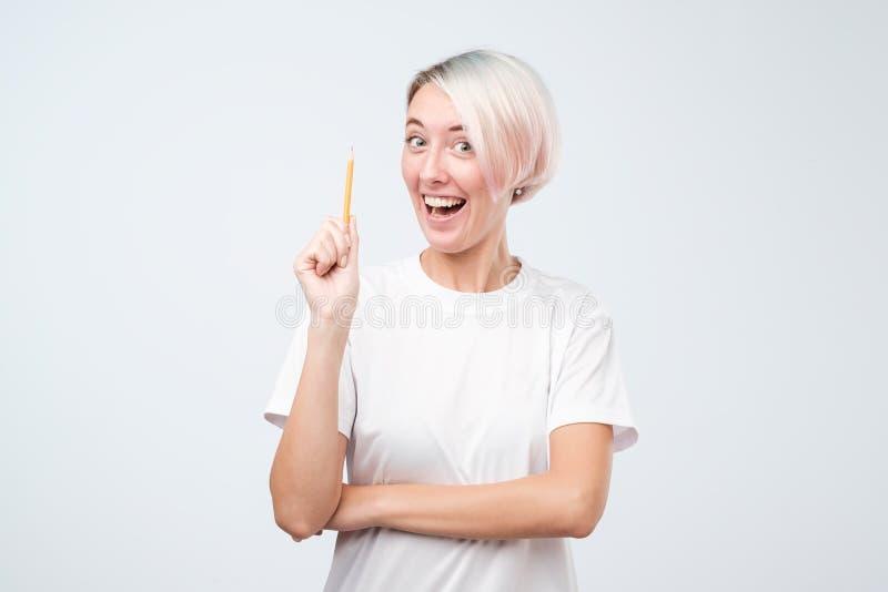 有想法和看照相机的愉快的少妇拿着铅笔 库存图片