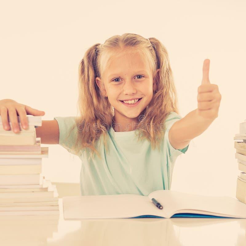 有愉快感觉的堆的逗人喜爱的微笑的小女孩的书 免版税库存照片