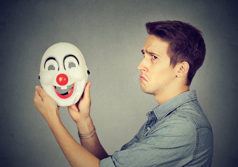 有愉快的小丑面具的年轻哀伤的人 人力的情感 免版税库存图片