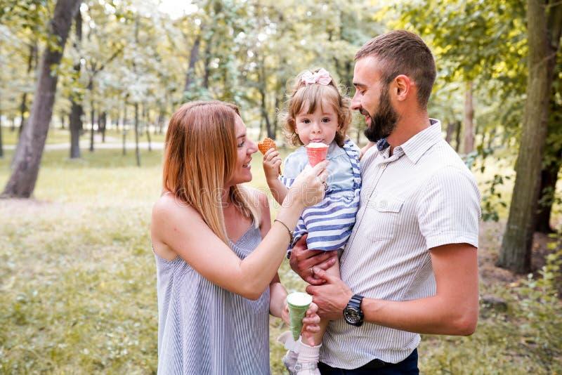 有愉快的年轻的家庭吃冰淇淋和乐趣外部 免版税库存图片