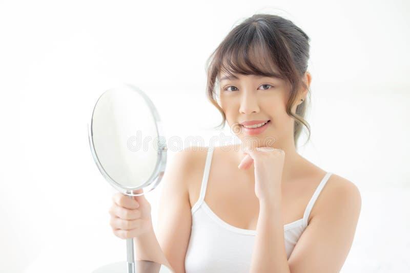 有愉快的微笑的和看的镜子的脸蛋漂亮年轻亚裔秀丽面部女孩妇女,构成有skincare的和化妆用品 免版税库存照片