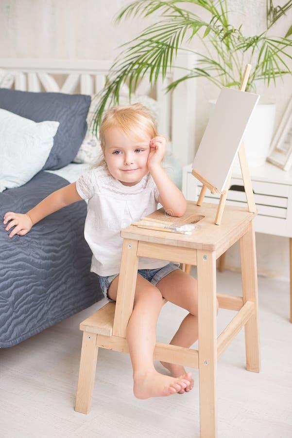 有愉快的微笑的满足的矮小的白肤金发的女孩 库存图片
