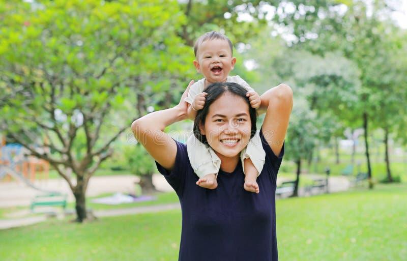 有愉快的男婴骑马的美丽的年轻亚裔母亲在妈妈的肩膀在自然公园 免版税库存照片