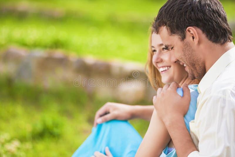 有愉快的笑的白种人的夫妇乐趣户外和Embracin 免版税库存照片