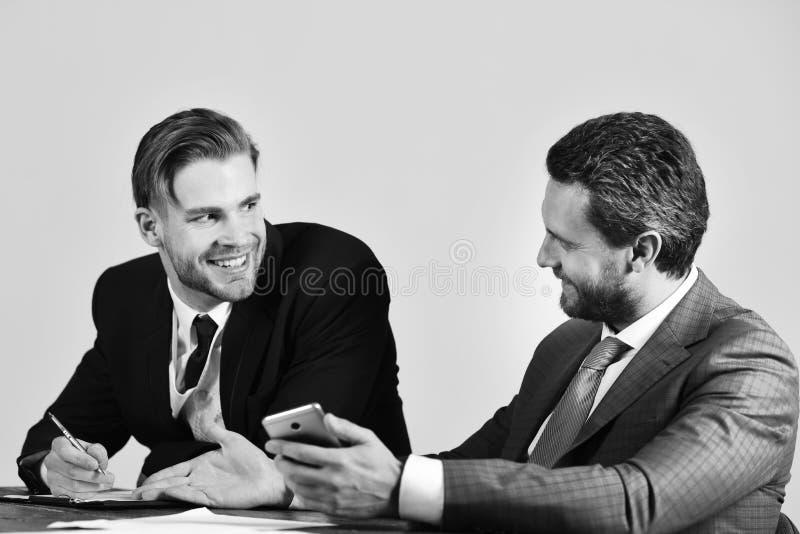 有愉快的面孔的经理谈论并且浏览互联网 免版税库存图片