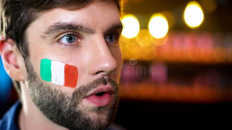 有意大利旗子的紧张的人在面颊观看的新闻,在电视的选举结果 免版税图库摄影
