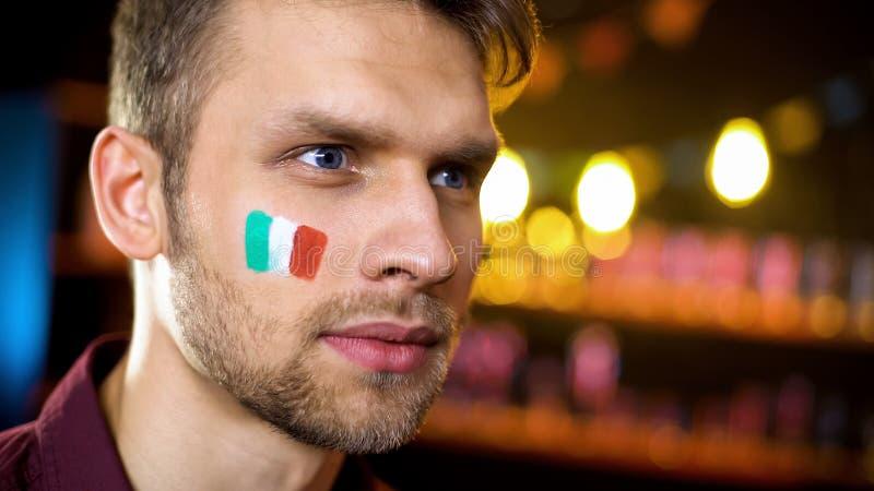 有意大利旗子的被集中的人在面颊殷勤地观看在酒吧的体育 库存图片