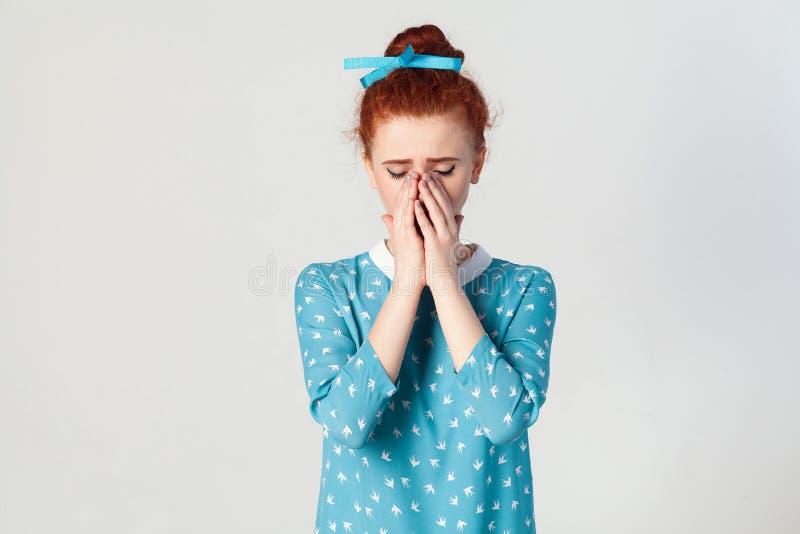 有感到姜的头发的沮丧和哭泣的年轻白种人女孩感到羞愧或恶心,盖面孔用两只手 库存照片