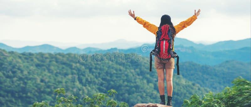 有感觉在山的背包冒险的妇女徒步旅行者或旅客战胜饰面,室外为在vacatio的教育自然 图库摄影