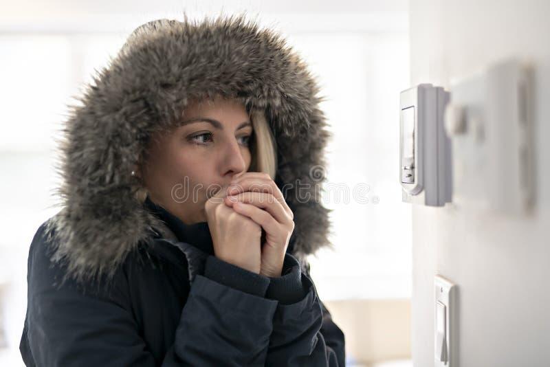 有感觉在议院里面的温暖的衣物的妇女寒冷 库存图片