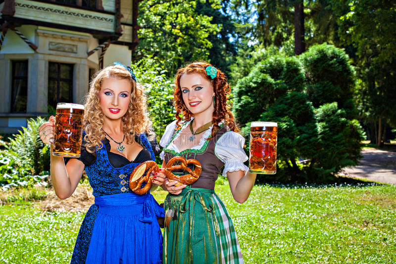 有慕尼黑啤酒节啤酒啤酒杯和椒盐脆饼的两个女孩 免版税库存图片
