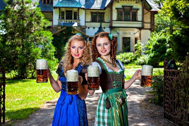 有慕尼黑啤酒节啤酒啤酒杯的两个女孩 库存照片