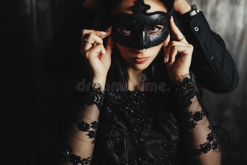 有戏剧性面具的妇女和英俊的人 免版税库存图片