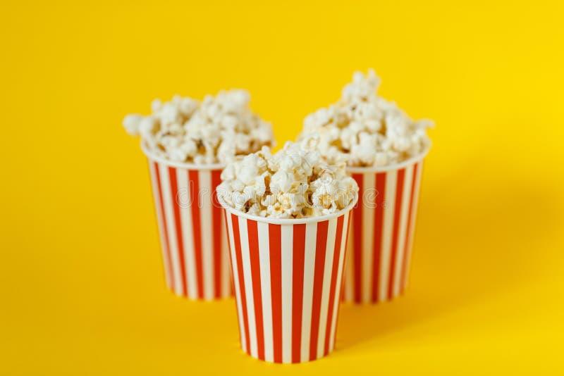 有戏院快餐的三个纸盒桶 玉米花和红色杯子在颜色黄色背景 免版税库存图片