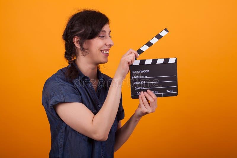 有戏院拍板身分的美丽的年轻女人在wonderfulyellow背景前面 图库摄影
