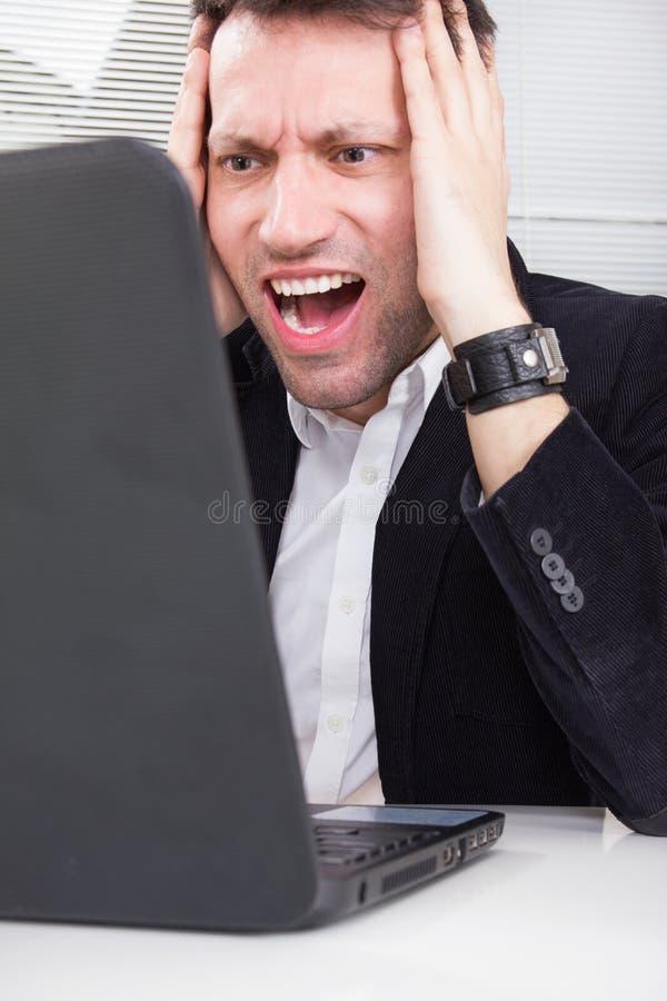 有成人的商人工作和使用膝上型计算机的问题 图库摄影