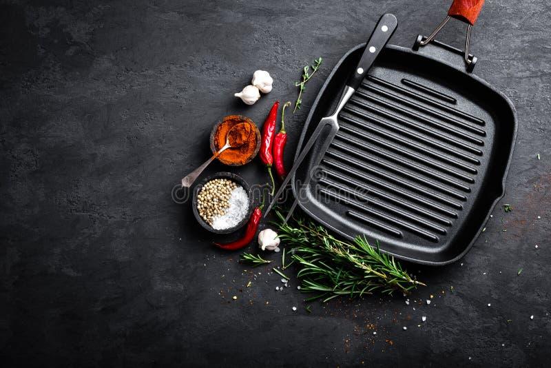 有成份的空的铸铁格栅平底锅烹调的在黑背景 免版税库存照片