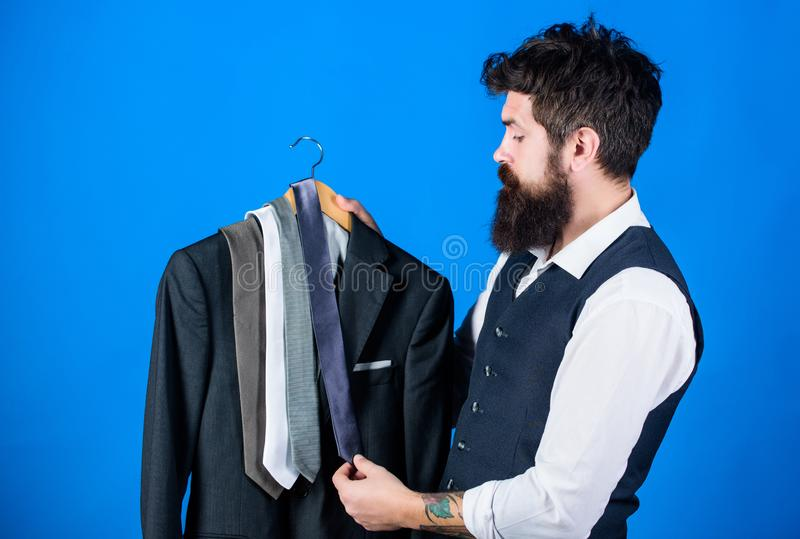 有成套装备的配比的领带 人有胡子的行家举行领带和正装 选择领带的人 完善的领带 免版税库存照片