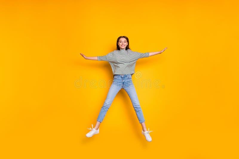 有成效星的跳跃的激动的女朋友全长身体尺寸照片,当隔绝与黄色生动时 免版税库存图片