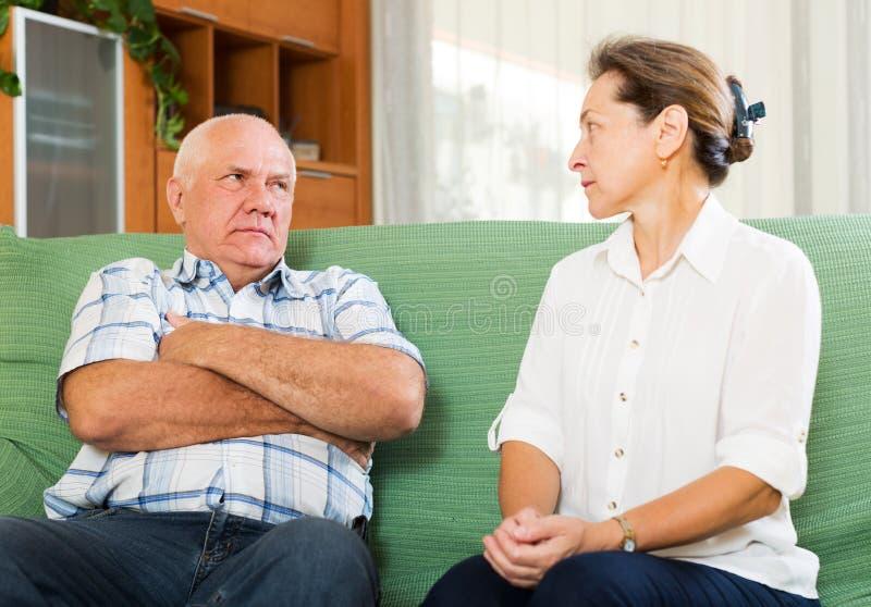 有成熟的夫妇严肃在家谈话 免版税图库摄影
