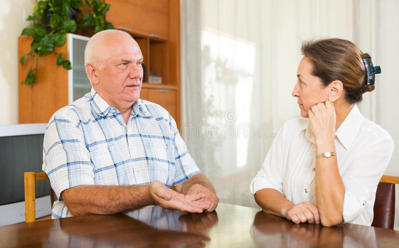 有成熟的夫妇严肃在家谈话 库存图片